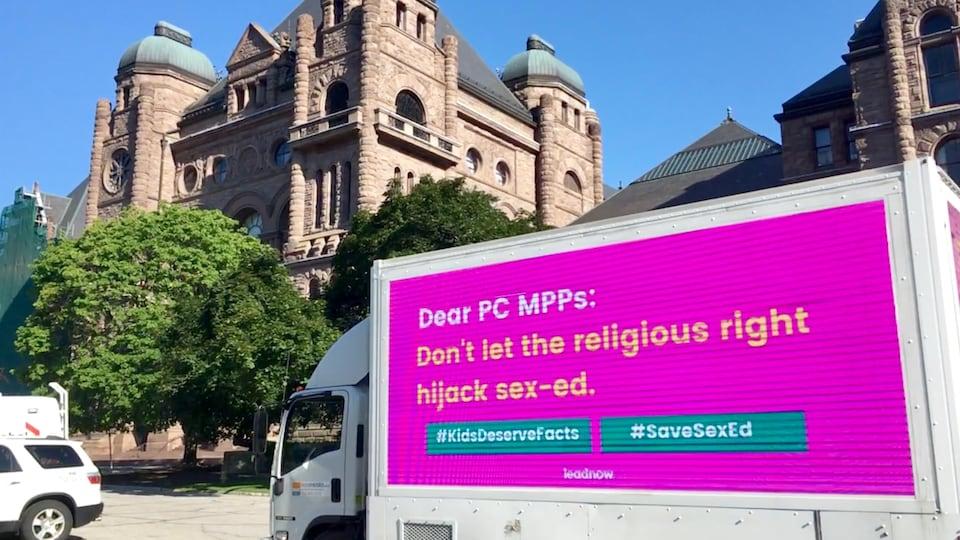 Une affiche sur un camion indique le message suivant: Chers députés provinciaux conservateurs, ne laissez pas la droite religieuse s'approprier le programme d'éducation sexuelle.