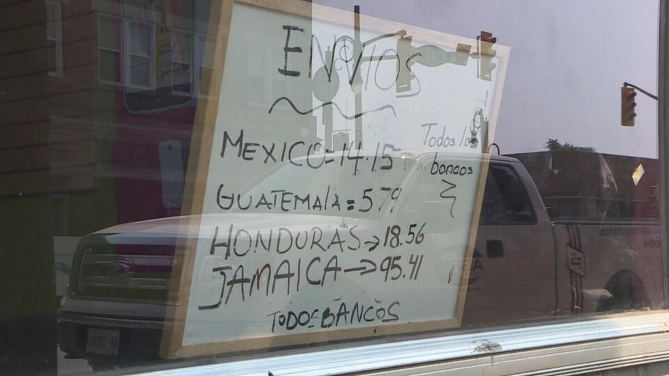 On voit dans une vitrine un tableau blanc avec des prix relié au Mexique, au Guatémala, au Honduras et à la Jamaïque.