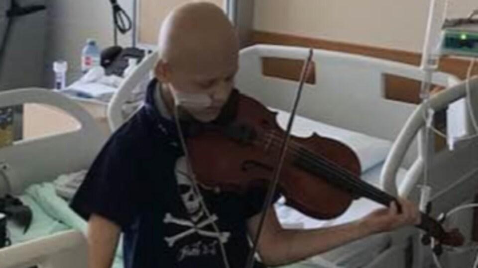 Un jeune garçon, sans cheveux, joue du violon, assis sur un lit d'hôpital.
