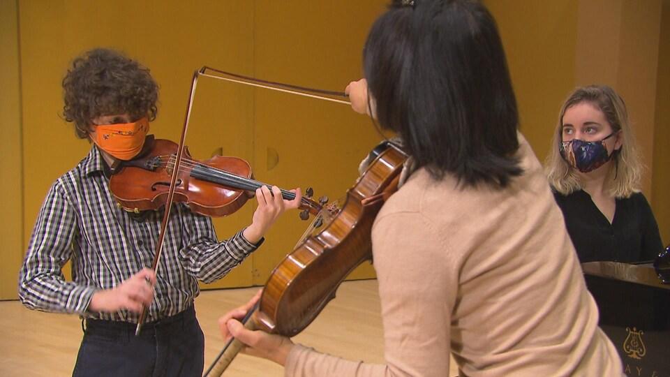 Le jeune Léandre tient son violon et écoute les conseils de la violoniste Ann Chow. Elle lui montre, avec son archet, où positionner le sien sur son violon.