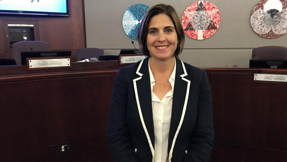 Isabelle LeBlanc debout et souriante au milieu de la salle du conseil municipal