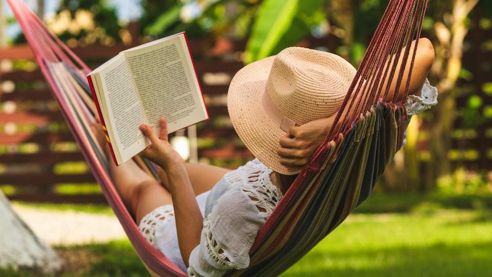 Une femme portant un chapeau lit un livre dans un hamac.