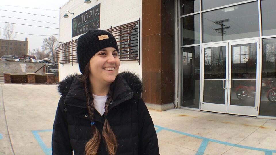 Une femme sourit devant une boutique de vente de cannabis médicinal.