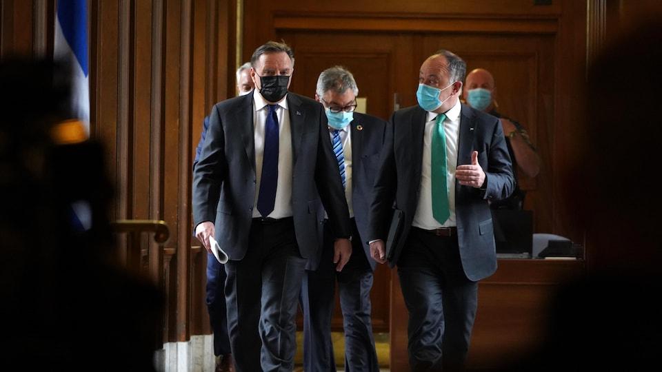 François Legault, Christian Dubé et Horacio Arruda marchent dans un couloir.