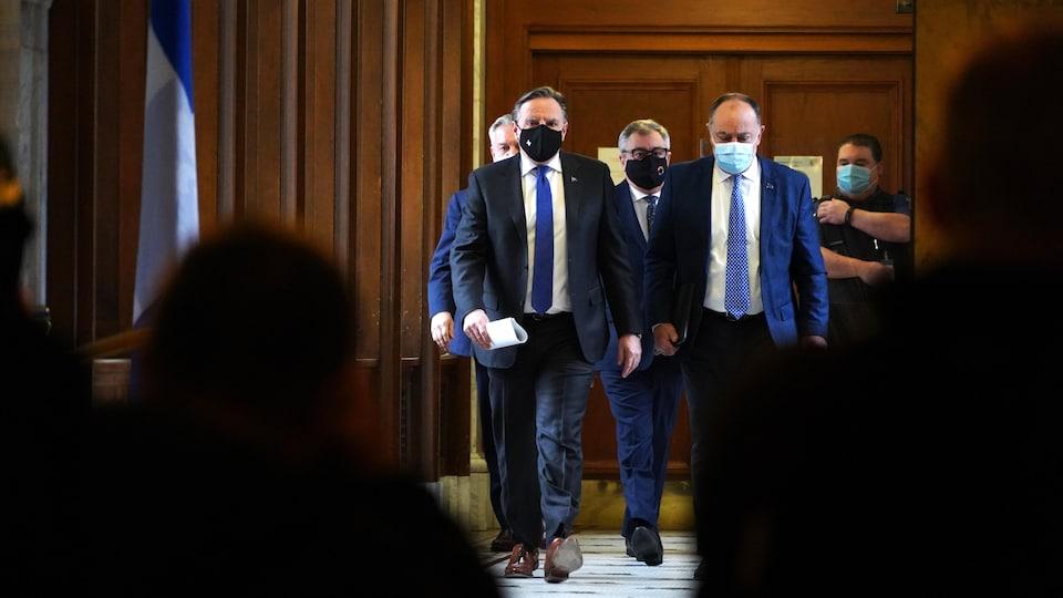 MM. Legault, Dubé et Arruda marchant dans un corridor de l'Assemblée nationale.