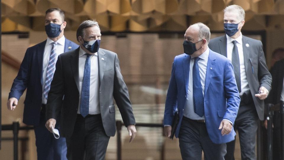 Les deux hommes marchent dans un corridor, escortés par deux agents de sécurité.