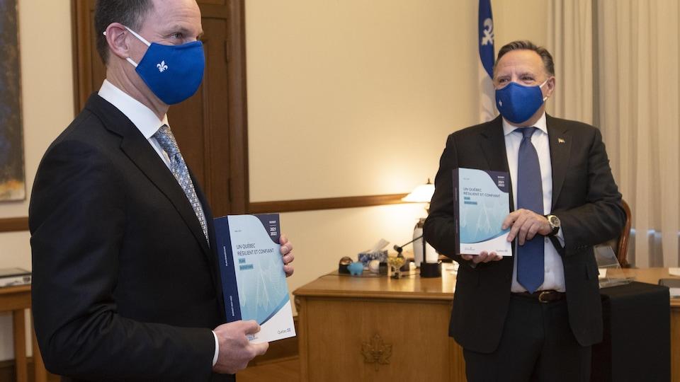 Les deux hommes tiennent des exemplaires du budget.