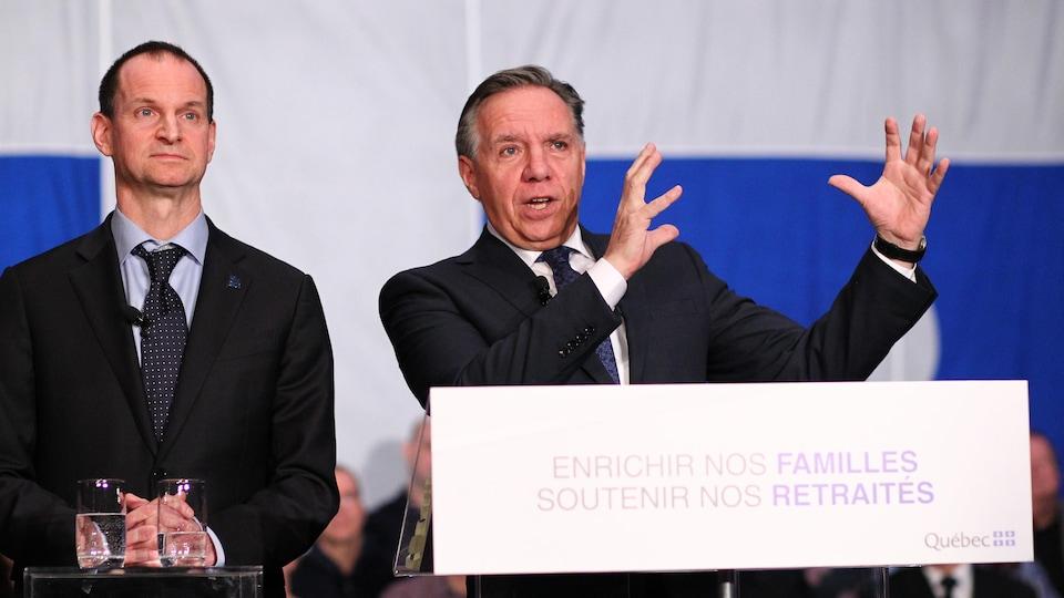 Le ministre québécois des Finances, Eric Girard, et François Legault se tiennent derrière un podium.