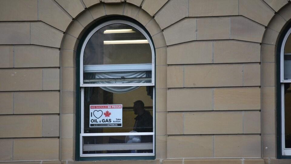 Une affiche « I love Oil and Gas » à une fenêtre du Palais législatif.