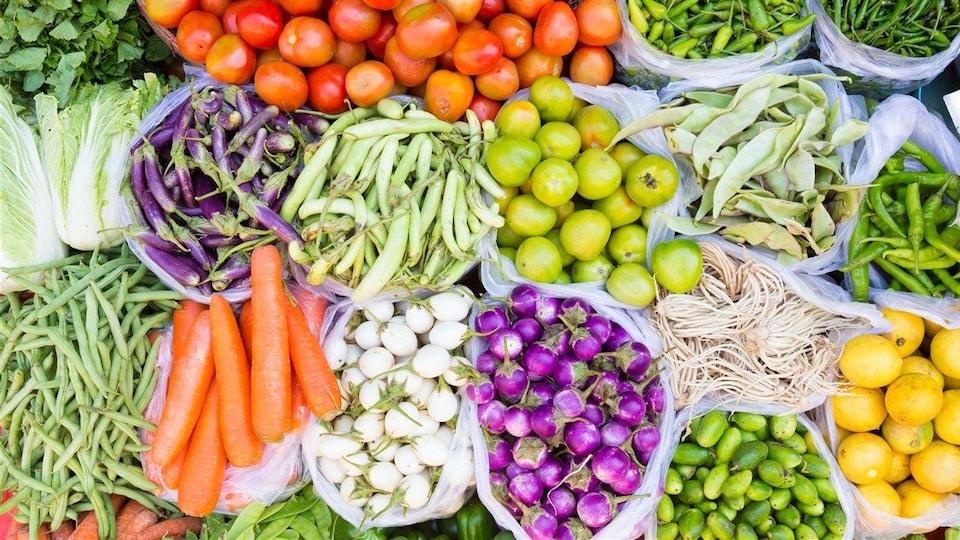 Divers légumes (pois, carottes, tomates, chous, etc.) sur l'étal d'un marché.