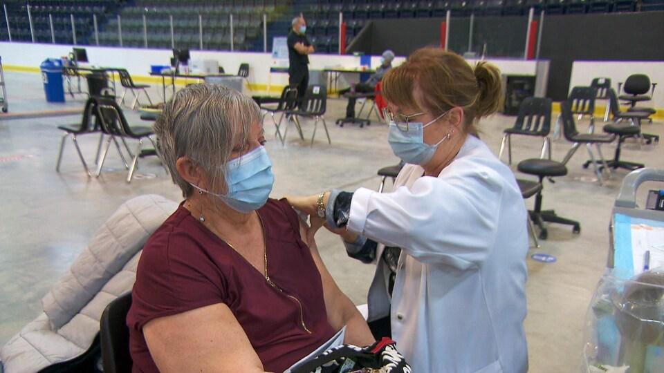 Une femme vaccine une autre femme sur la glace du Colisée Béton provincial, à Matane.