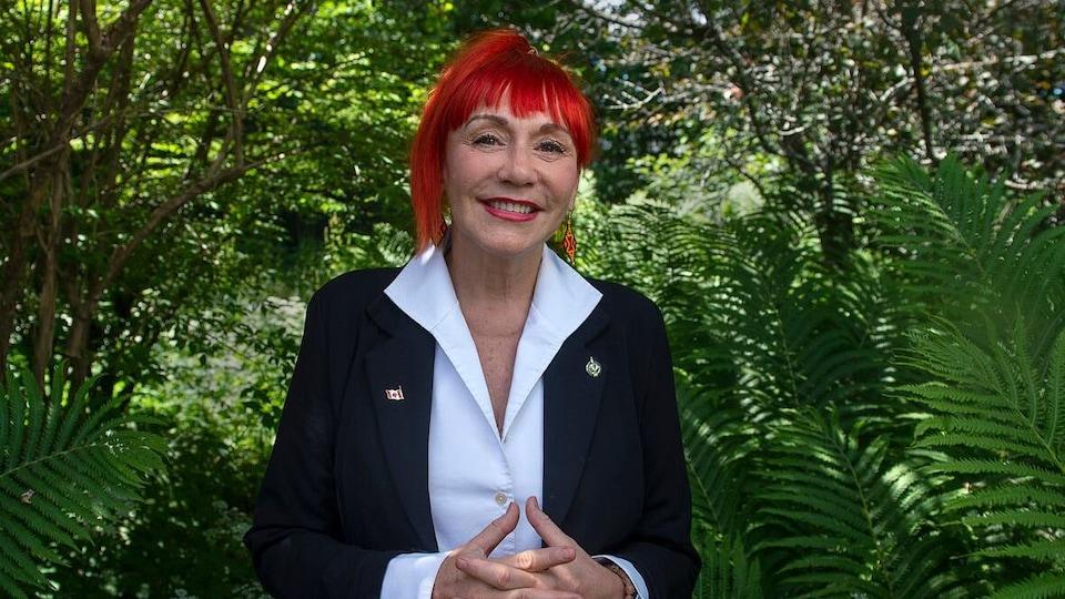 Lenore Zann devant des plantes vertes.