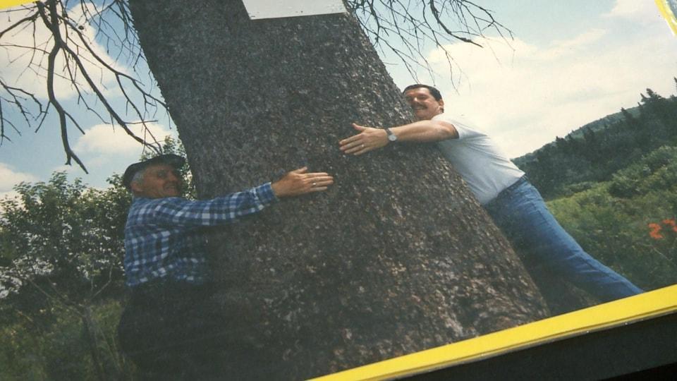 Léonard Otis et un autre homme enlacent un arbre.