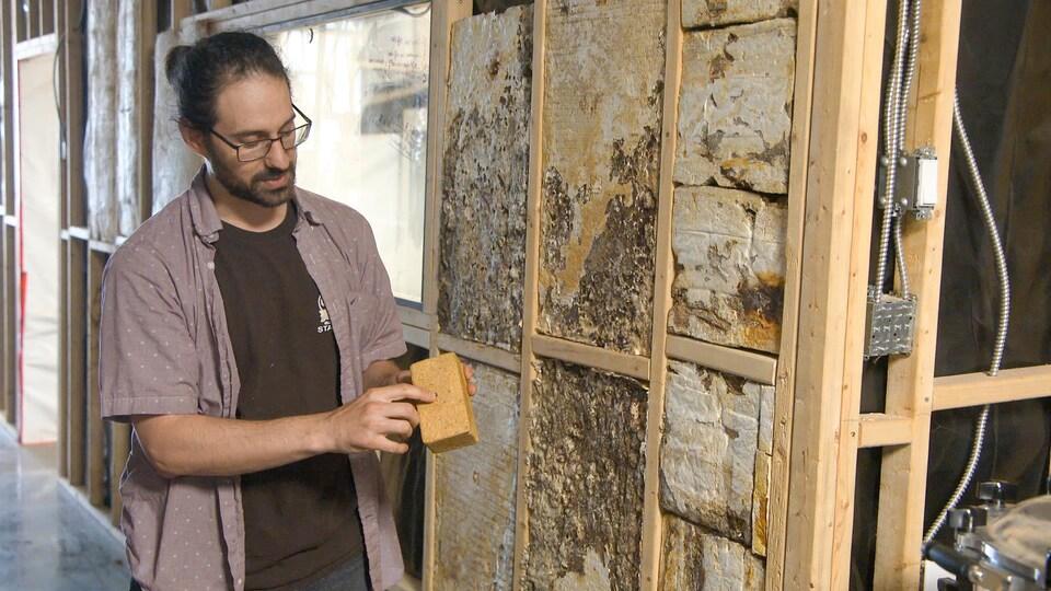 Un homme montre une brique fabriquée à l'aide de champignons.