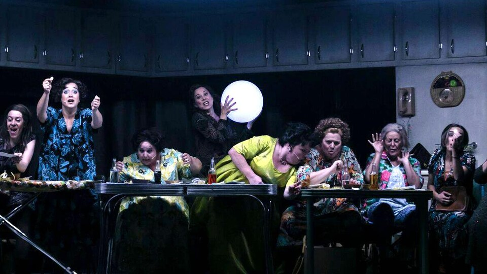 Plusieurs femmes sont assises devant une table et boivent.