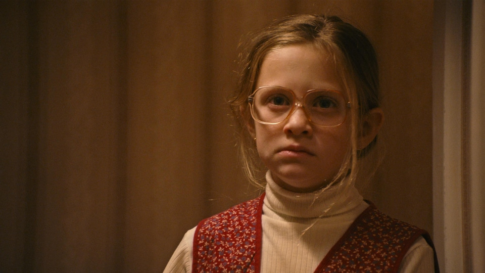 La fillette blonde porte des lunettes et ne paraît pas contente.