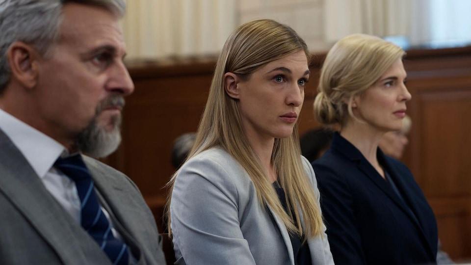 Les trois personnes sont assises côte à côte.