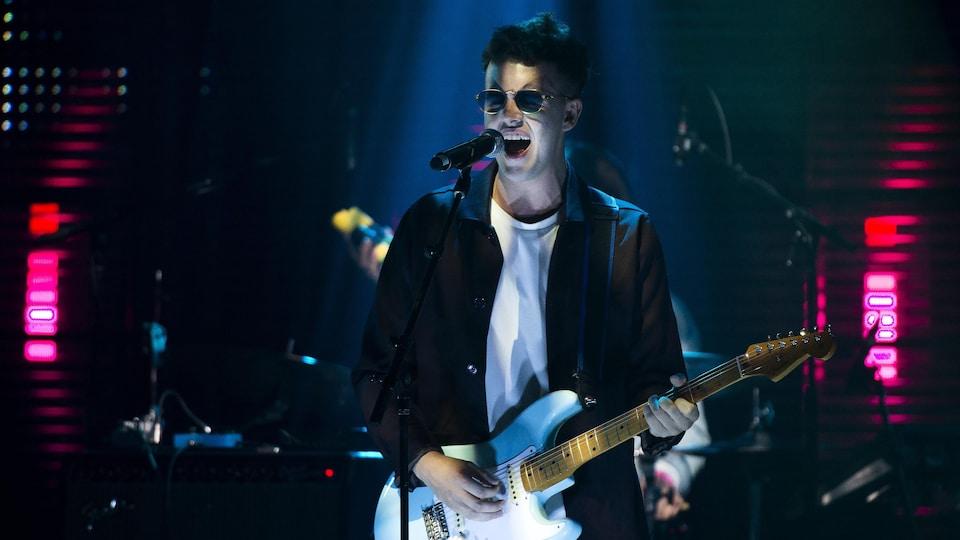 Un chanteur qui joue de la guitare sur scène.