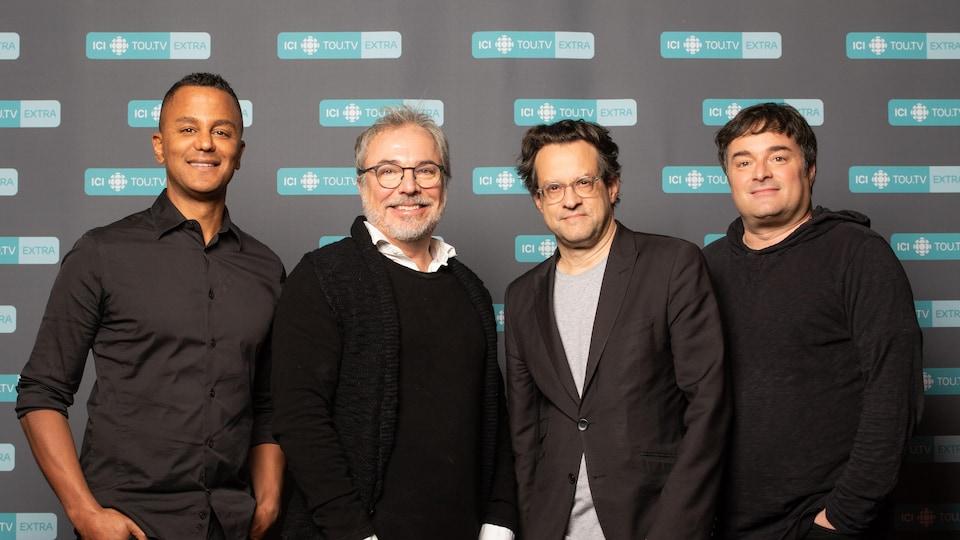 Les quatre hommes sourient à la caméra.