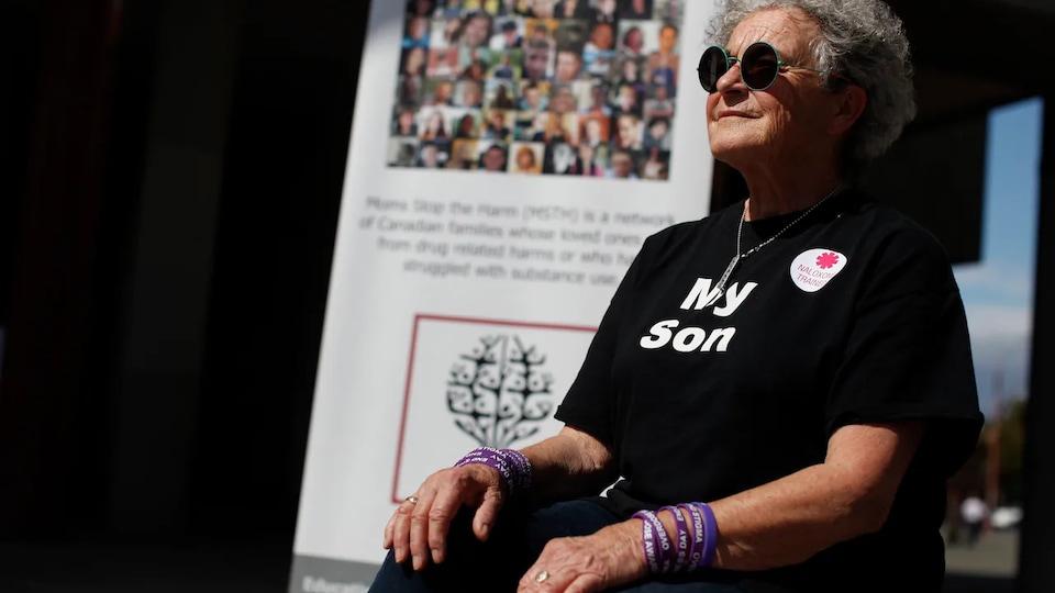 Une dame âgée avec des verres fumés et un t shirt noir sur lequel il est écrit en anglais: mon fils, est assise devant une affiche avec plusieurs photographies de visages.