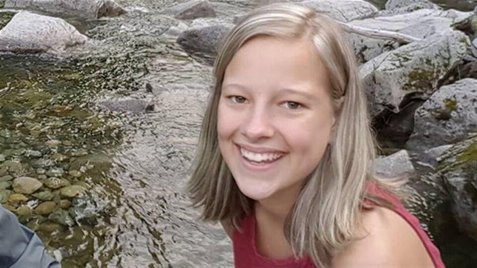 Gros plan du visage d'une jeune fille aux cheveux blonds qui sourit avec, en arrière-plan, un ruisseau et des rochers.