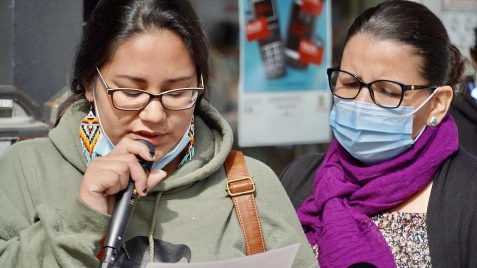 Une dame lit une lettre au micro, accompagnée d'une autre personne.