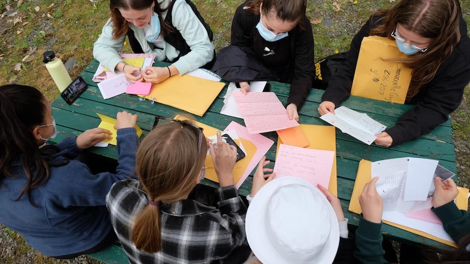 Sept amies lisent leur lettre ensemble.
