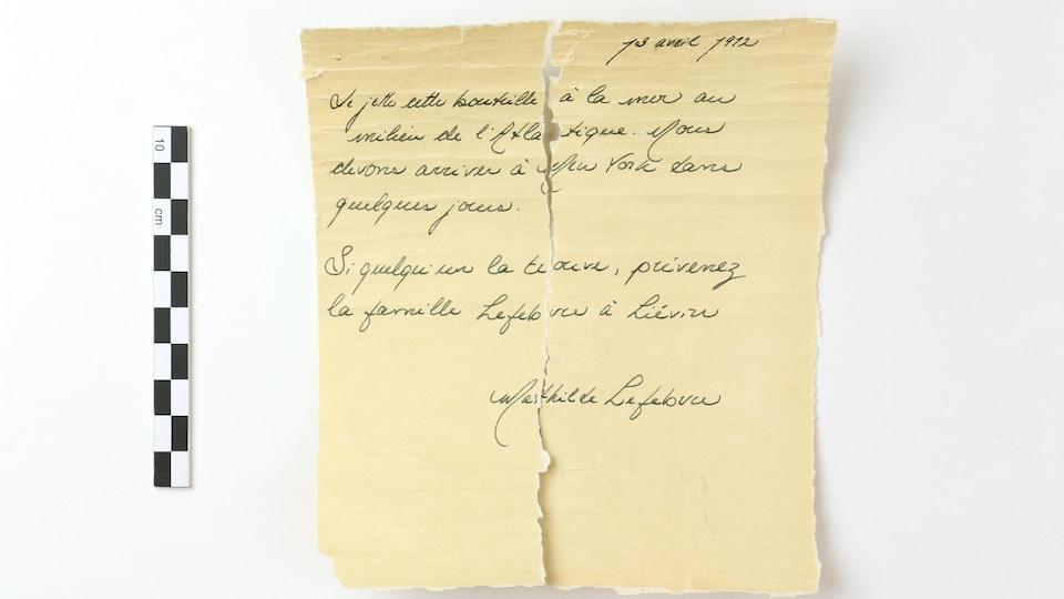Une lettre déchirée en partie sur un fond blanc.