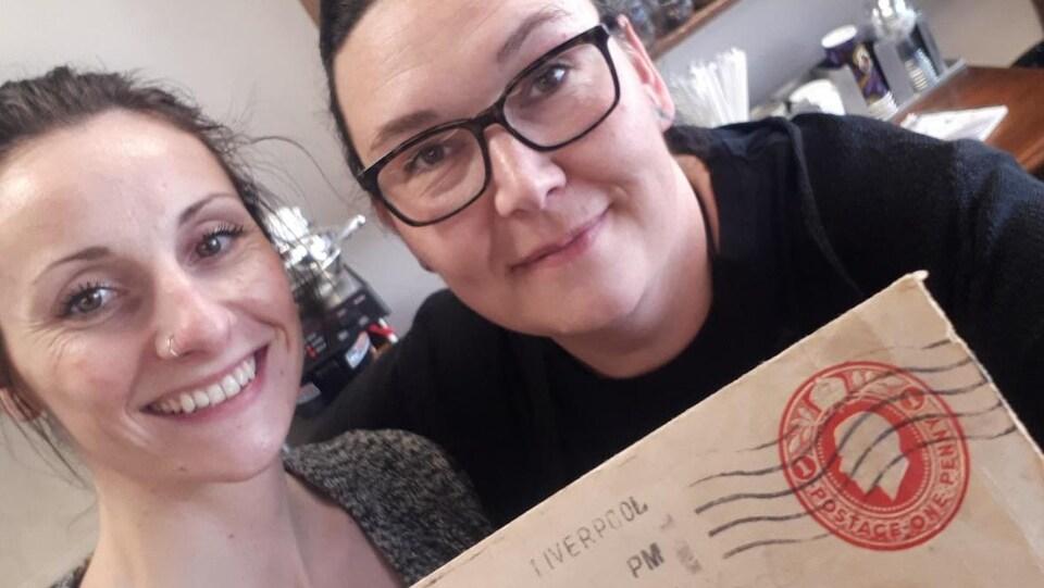 Deux femmes posent avec une lettre dans un café.
