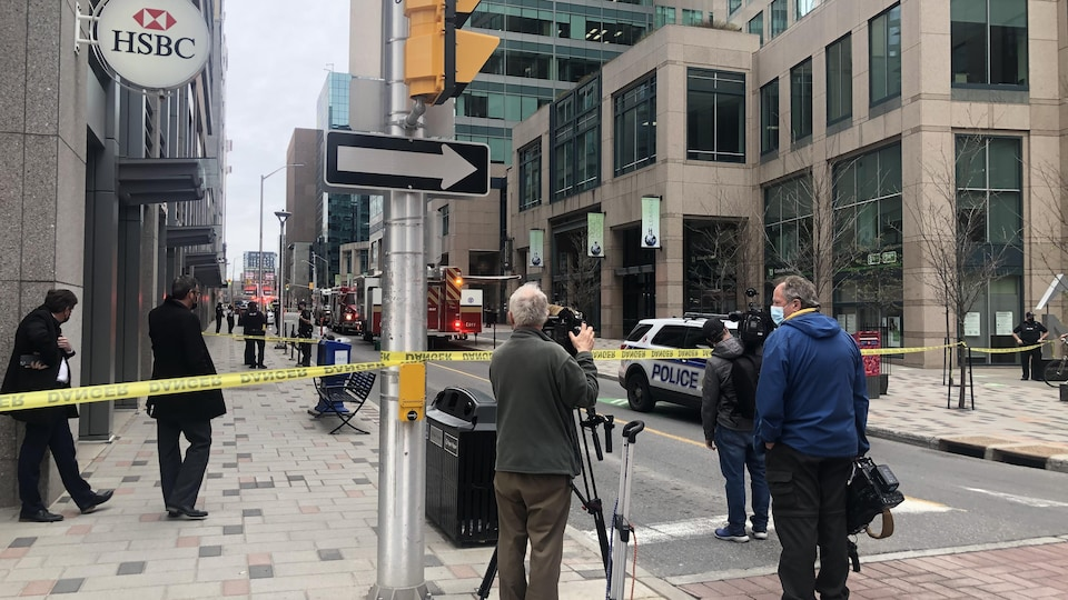Des caméramans tournent des images, derrière le ruban jaune des policiers.