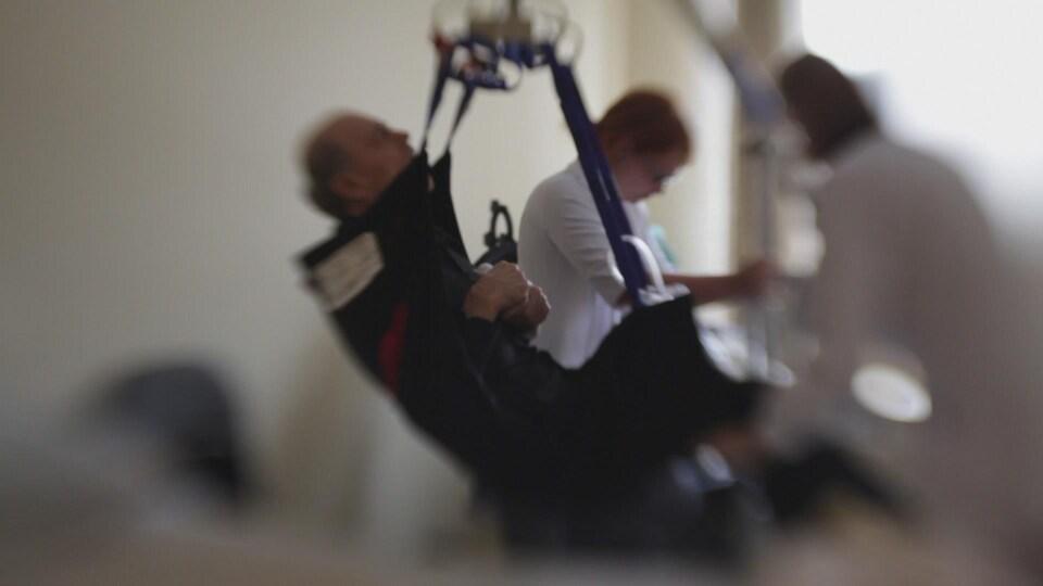 Des employés d'un CHSLD utilisent un lève-personne pour soulever un résident.