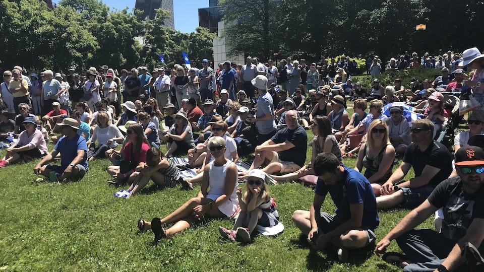 Le public est assis sur la pelouse et regarde vers l'avant. Plusieurs personnes tiennent un drapeau du Québec.