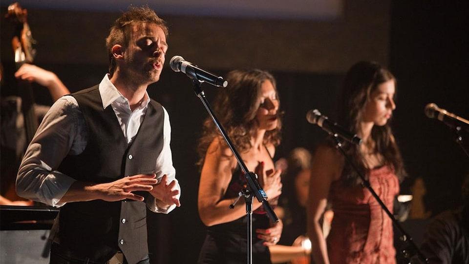 Trois artistes chantent devant un micro.