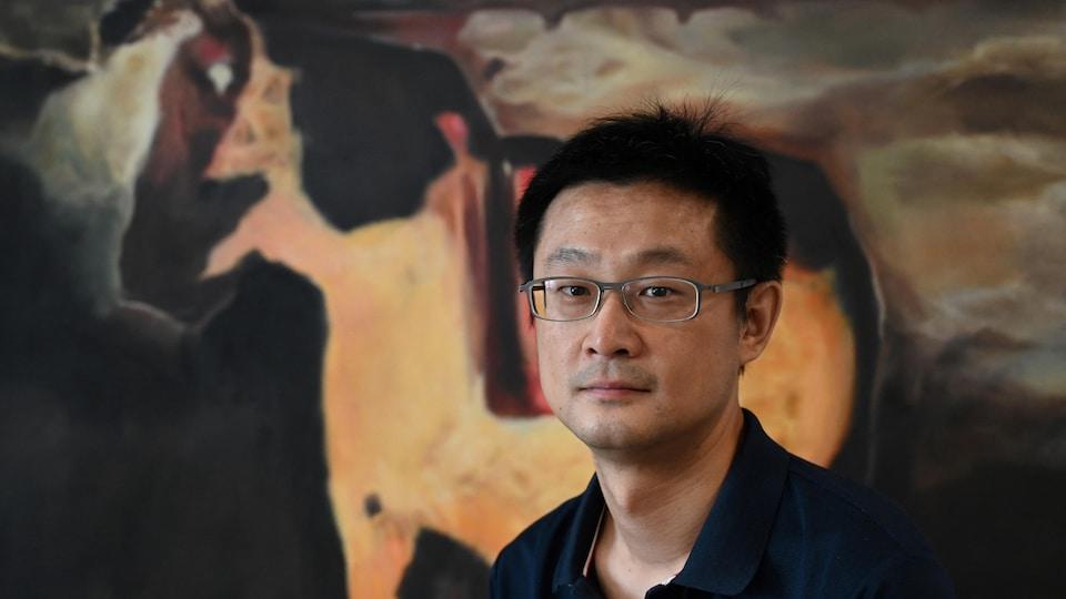 Portrait de l'homme qui regarde devant lui avec une image non distincte en arrière-plan.