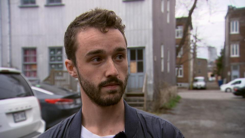 Liam Garneau accorde une entrevue à Radio-Canada dans une ruelle du quartier Limoilou.