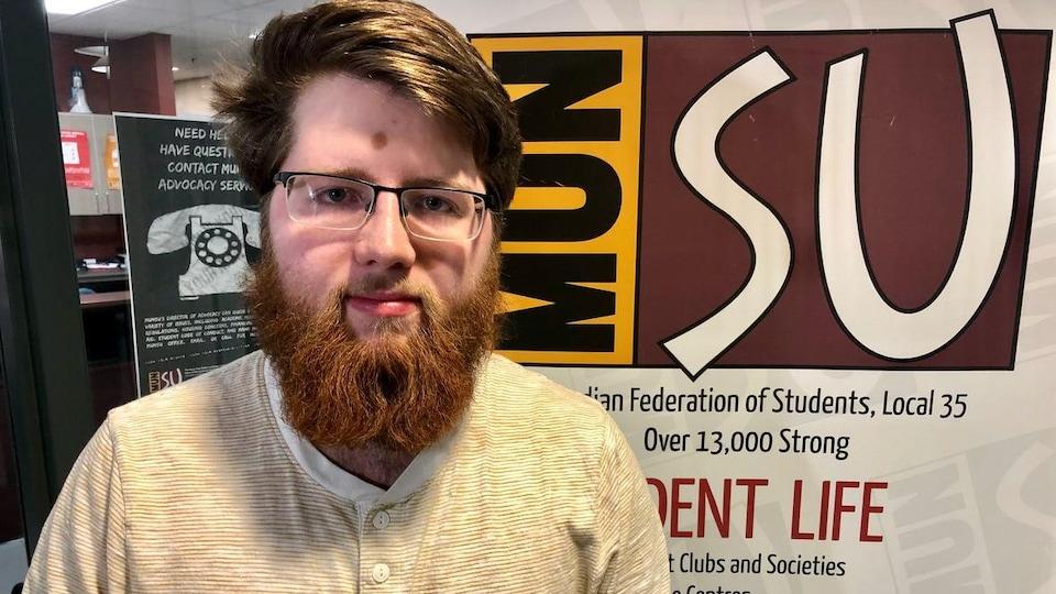 Liam O'Neill devant une affiche de l'association étudiante MUNSU.