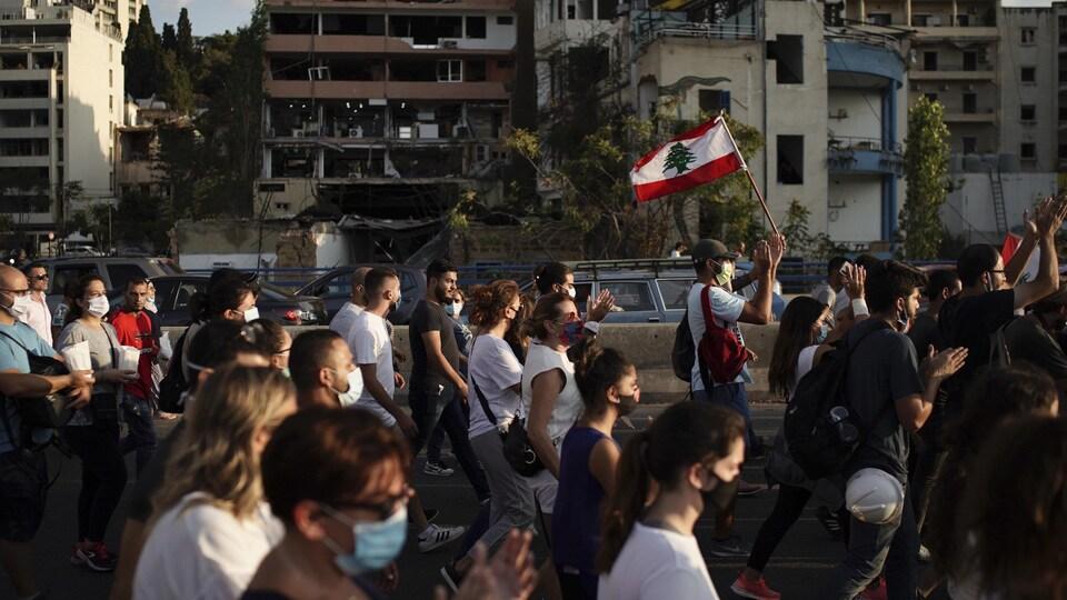 Des gens marchent devant des immeubles en ruines.