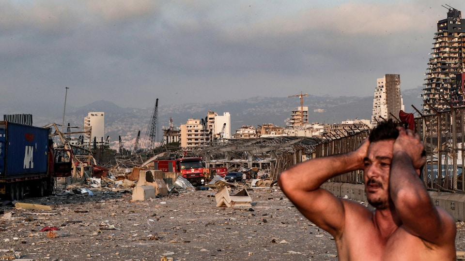 Une homme se prend la tête devant de nombreux immeubles en ruines.