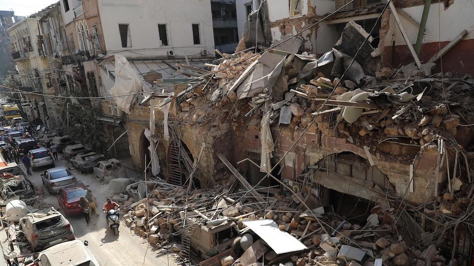 Une rue où plusieurs immeubles sont en ruines, plein de débris étant tombés sur des voitures.