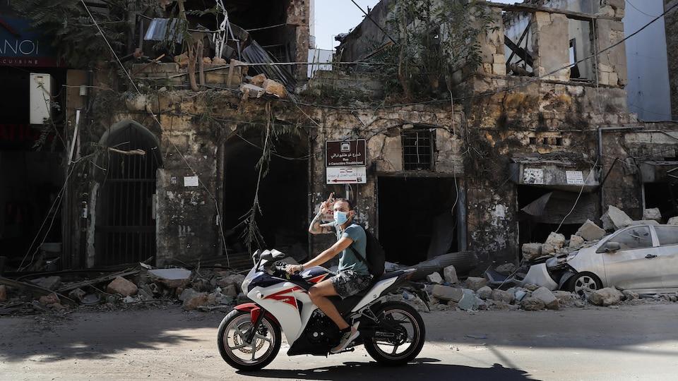 Un motocycliste passe devant des ruines, à Beyrouth.