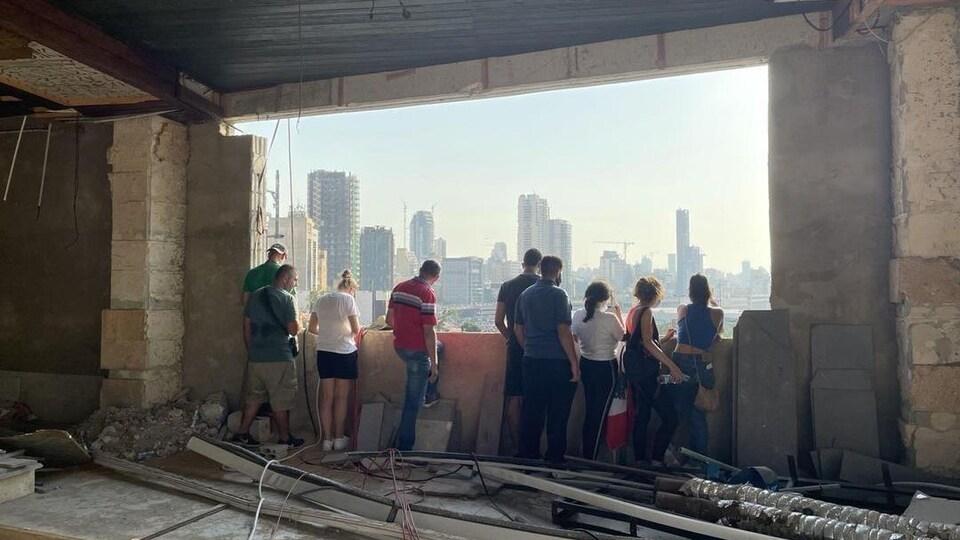 Des Libanais regardent Beyrouth par une grande fenêtre dans un bâtiment endommagé ou en construction.