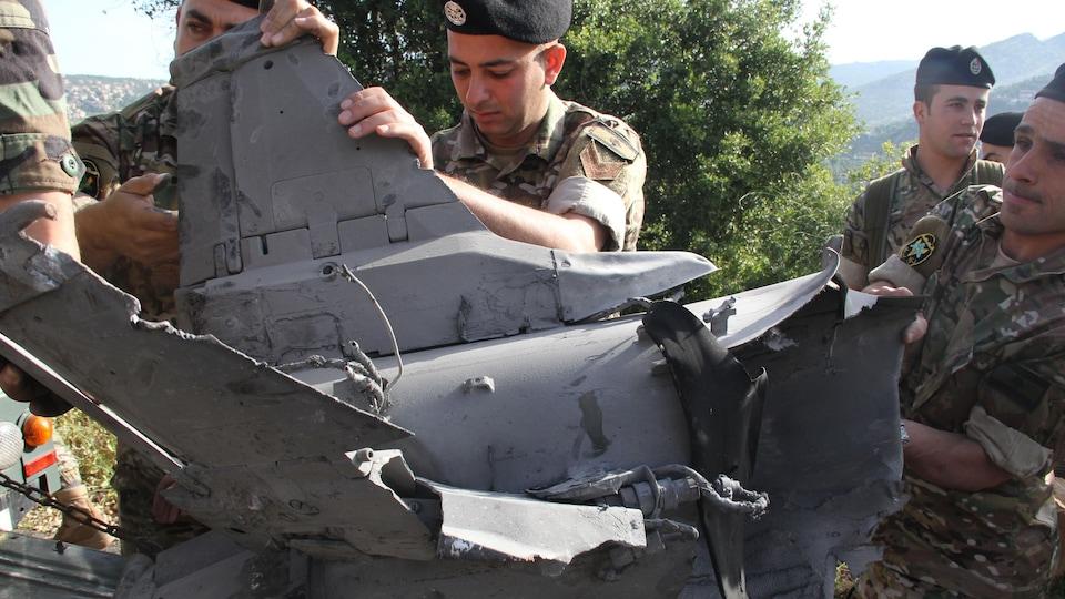 Plusieurs soldats tiennent et observent la carcasse d'un missile.