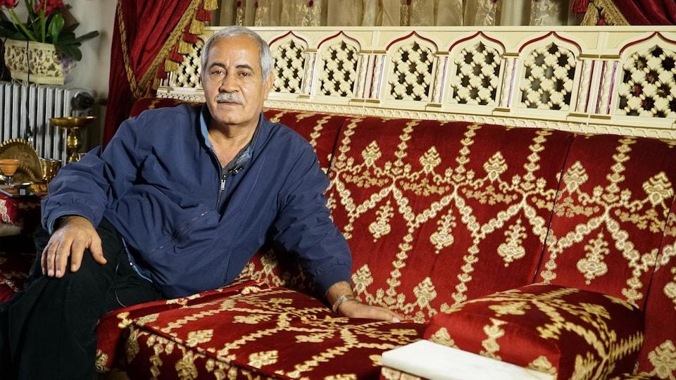 Talal Chreif, est assis sur un sofa.