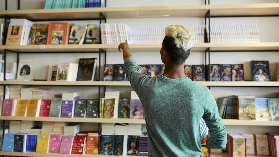 Un homme prend des livres sur une étagère.