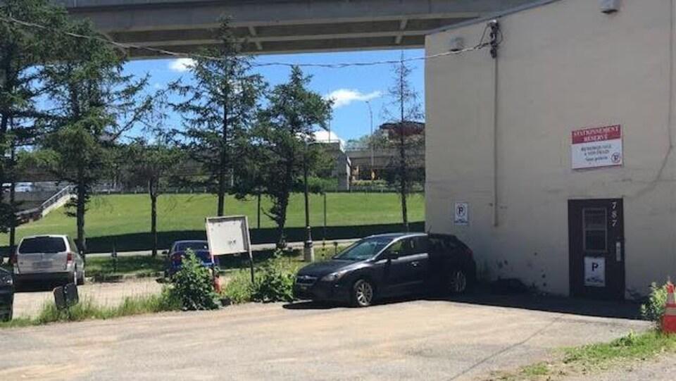 Vue sur un terrain du quartier Saint-Roch sur lequel un stationnement a été aménagé. On aperçoit des voitures ainsi que la façade nord d'un bâtiment. À l'arrière-plan, on distingue les piliers de l'autoroute Dufferin-Montmorency.