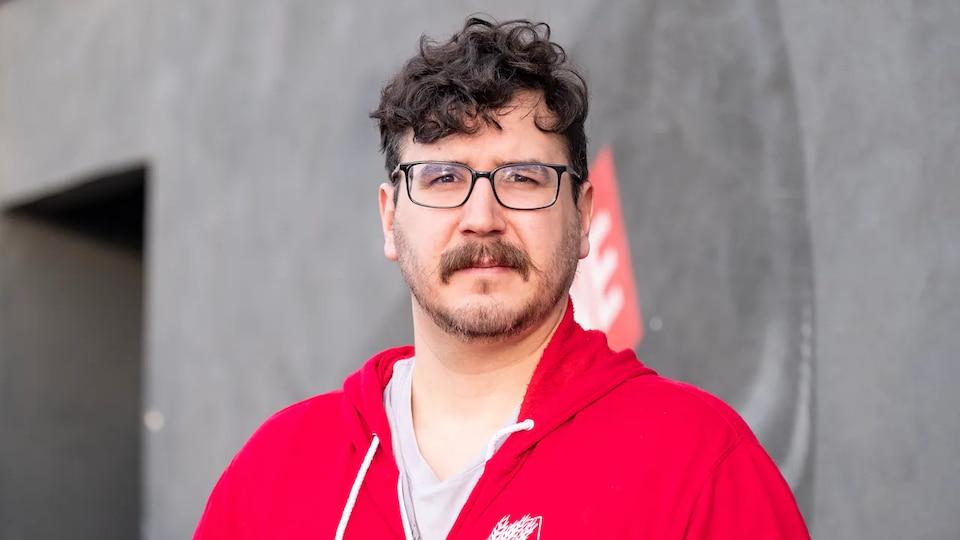 Un homme porte des lunettes de vue et une moustache.