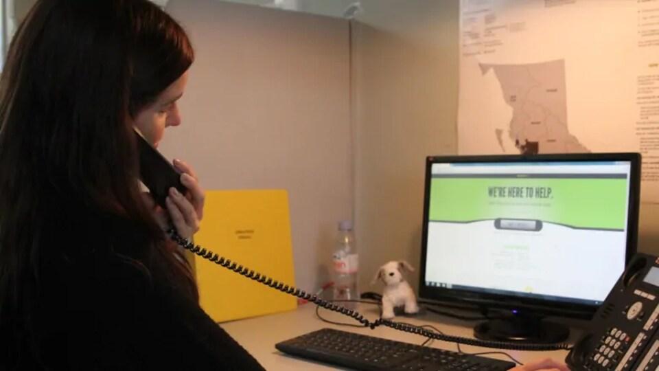 Une femme est installée à un bureau où se trouve un ordinateur. Elle parle au téléphone.