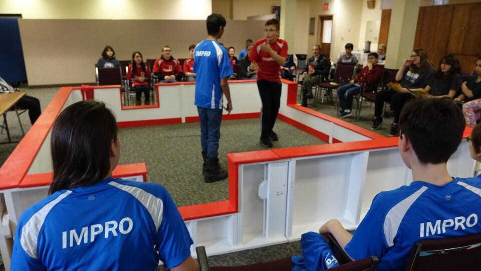 Deux élèves regardent deux autres élèves au milieu d'un ring improvisé.