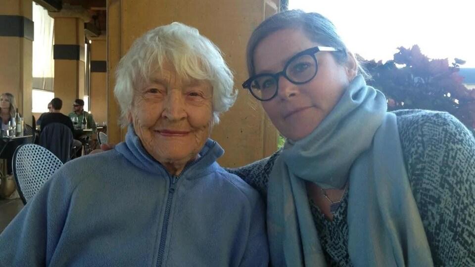 Une femme âgée et une femme plus jeune posent ensemble.