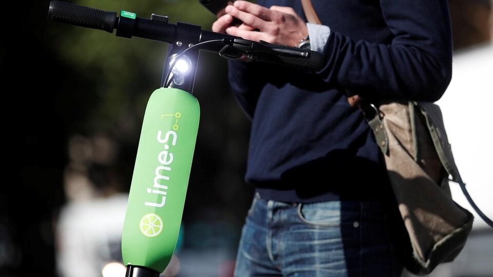 Un homme regarde son cellulaire près d'une trottinette électrique de marque Lime.